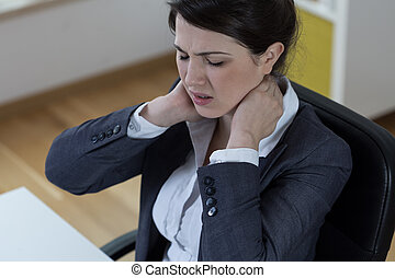 Sitting woman with pain - Young sitting woman in office with...