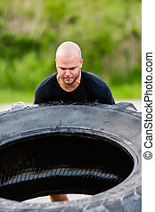 Determined Athlete Flipping Truck Tire - Determined young...