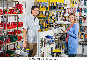 Couple Buying Tools In Hardware Store - Portrait of smiling...