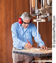 Senior Carpenter Cutting Wood With Bandsaw - Senior...