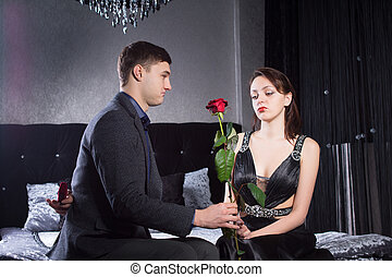 Young Man Offering Rose Flower to Sad Girlfriend