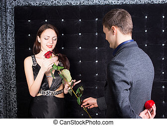 Young man proposing to his sweetheart first offering her a...