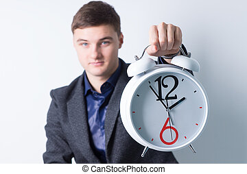 Young Man Showing Alarm Clock at the Camera - Handsome Young...