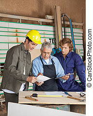 Carpenter Holding Digital Tablet While Discussing With...