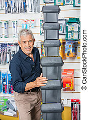 Confident Senior Man Stacking Toolboxes In Store - Portrait...