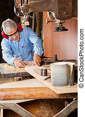 Carpenter Using Bandsaw To Cut Wood - Senior carpenter using...