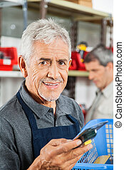 Confident Senior Salesman Holding Tool In Store - Portrait...