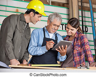 Carpenters Using Tablet Computer In Workshop - Male and...