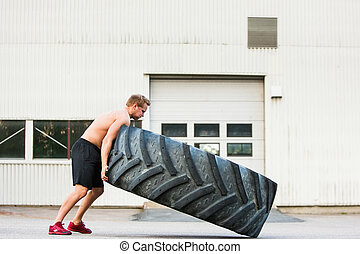 Male Athlete Flipping Large Tire - Full length side view of...