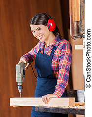 Female Carpenter Using Drill Machine On Wood - Portrait of...