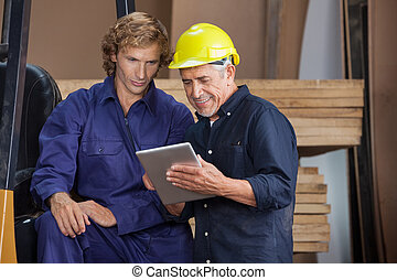 Carpenter Using Digital Tablet With Colleague