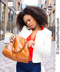 young woman on the phone loonking in her handbag