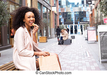 young woman having a healthy snack in the street