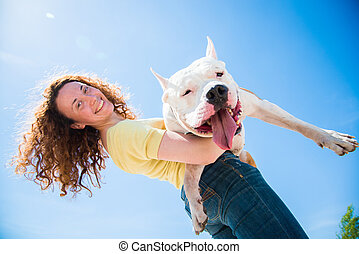 dog - A girl holds a huge dog breed Staffordshire Terrier