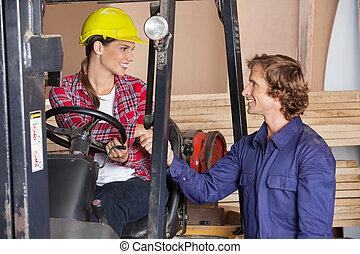 Supervisor In Forklift Shaking Hands With Carpenter
