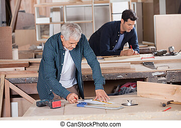 Senior Carpenter Drawing Diagram On Blueprint - Senior male...