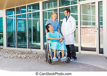 Nurse And Doctor Looking At Patient On Wheelchair Outside...
