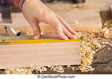 Carpenters Hand Measuring Wood With Scale - Closeup of...