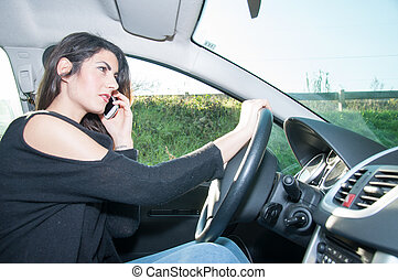 female driver with his smart phone in a sunny day