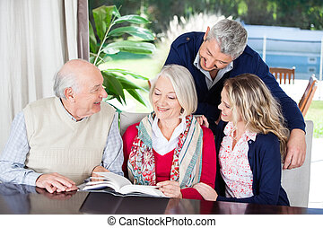 Happy Couple With Grandparents Reading Book In Nursing Home...