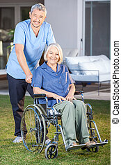 Male Nurse Standing With Senior Woman On Wheelchair - Full...