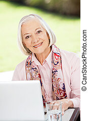 Happy Senior Woman With Laptop At Nursing Home Porch