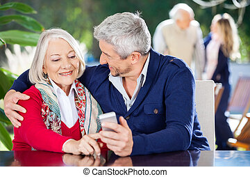 Affectionate Grandson And Grandmother Using Smartphone -...