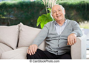 Happy Senior Man Sitting At Nursing Home Porch