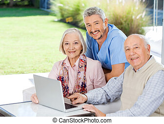 Caretaker And Senior Couple With Laptop At Nursing Home -...