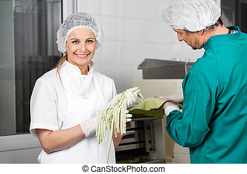 Smiling Chef Holding Spaghetti Pasta With Colleague Working...