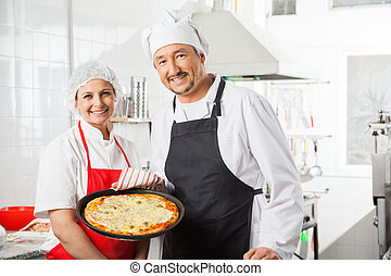 Confident Chefs With Pizza Pan At Commercial Kitchen -...