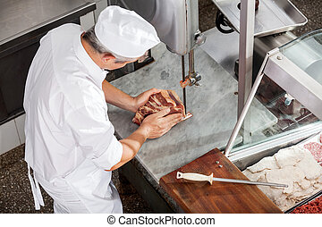Butcher Cutting Meat With Bandsaw - High angle view of...