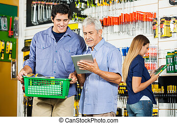 Father And Son Using Digital Tablet In Hardware Store -...