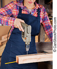 Female Carpenter Using Drill Machine On Wood - Midsection of...