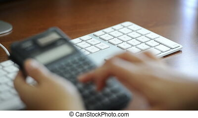Accounting - An accountant enters expenses on a calculator...
