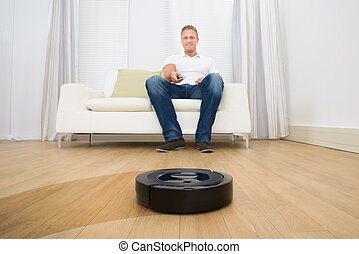 Man Holding Remote Control Of Robotic Vacuum Cleaner - Happy...