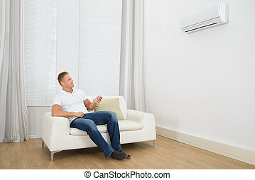Man Adjusting The Temperature Of Air Conditioner - Man...