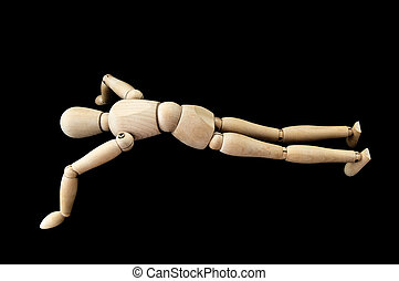 jointed wooden man doing push-ups with black isolated background