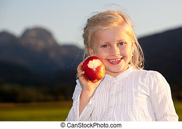 Child outside with red apple - Child is holding a red apple...