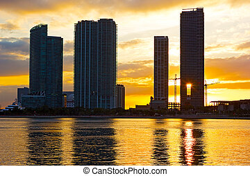 Skyscrapers near the waterfront with bright sunset at the...