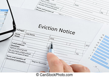 Hand With Pen And Eyeglasses Over Eviction Notice - Close-up...