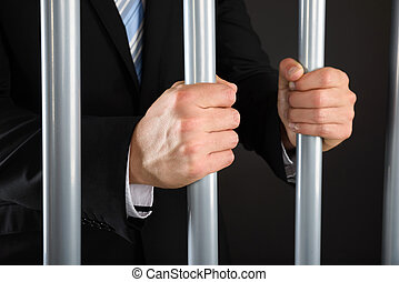 Close-up Of Businessman Holding Bars In Jail