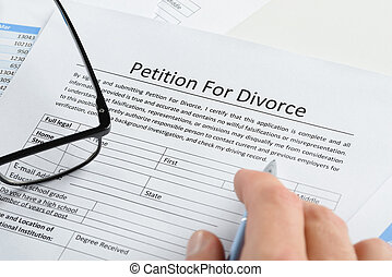 Hand With Pen On Petition For Divorce Paper - Close-up Of...