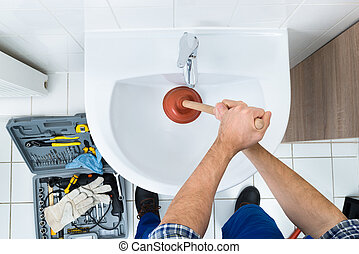 Male Plumber Using Plunger In Bathroom Sink - High Angle...