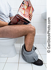 Man In Toilet Holding Sexy Magazine - Close-up Of A Man...