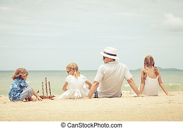 Father and children playing on the beach at the day time...