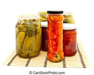 glass jars with marinated vegetables and fruit jam at the...