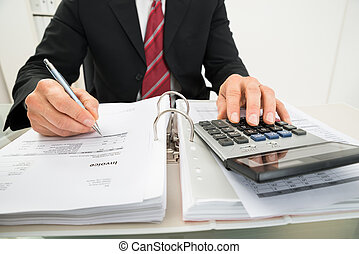 Businessman Calculating Invoice At Office Desk - Close-up Of...