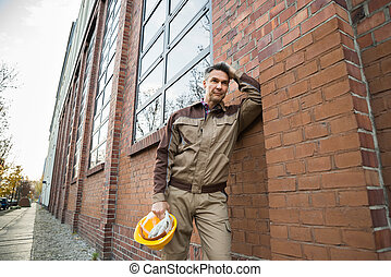 Portrait Of Thoughtful Builder Leaning On Brickwall
