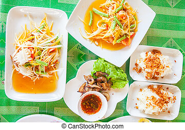 Papaya salad (som tum Thai) with sticky rice and grilled...